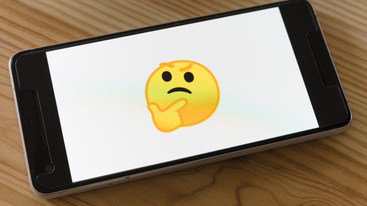 black flat screen tv turned on displaying yellow emoji